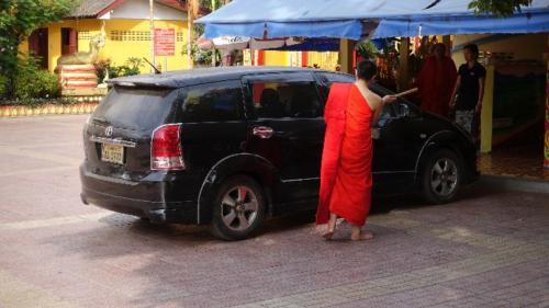 Vientian – mnich buddyjski naterenie świątyni błogosławiący nowy luksusowy samochód